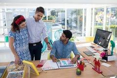 Équipe de concepteurs discutant au-dessus du document photographie stock