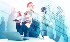 Équipe de directeur avec l'ordinateur portable, fond de gratte-ciel images stock