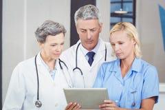 Équipe de docteur utilisant le comprimé numérique photos stock