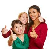Équipe de filles multiculturelles tenant des pouces  Photographie stock