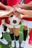 Équipe de football empilant des mains sur la boule Photographie stock