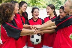 Équipe de football enthousiaste empilant des mains sur la boule Images stock