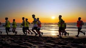 Équipe de football pulsant et s'exerçant sur la plage Photographie stock libre de droits