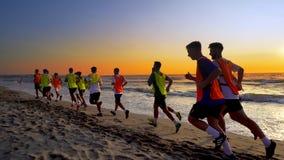 Équipe de football pulsant et s'exerçant sur la plage au lever de soleil Photos stock