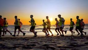 Équipe de football s'exerçant et courant extérieur sous le coucher du soleil de plage Image stock