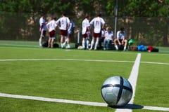 Équipe de football se reposant sur le fond Photographie stock libre de droits