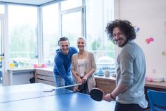 Équipe de jeune entreprise jouant le tennis de ping-pong Photographie stock libre de droits