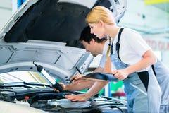 Équipe de mécanicien travaillant dans l'atelier de voiture Photos stock