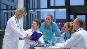 Équipe de médecins ayant une réunion dans la salle de conférence banque de vidéos