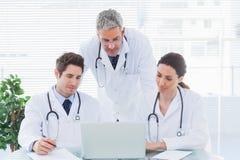 Équipe de médecins concentrés collaborant avec leur ordinateur portable images stock