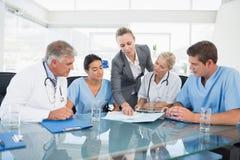 Équipe de médecins et de femme d'affaires ayant une réunion photos libres de droits