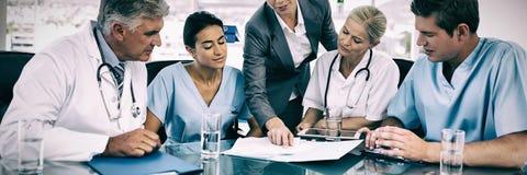 Équipe de médecins et de femme d'affaires ayant une réunion image libre de droits