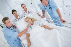 Équipe de médecins portant le patient sur la civière photographie stock libre de droits