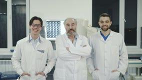 Équipe de médecins réussis regardant et souriant l'appareil-photo 4K clips vidéos