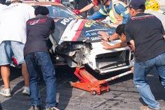 Équipe de personnel poussant la voiture de course détruite Photographie stock