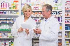 Équipe de pharmaciens agissant l'un sur l'autre au sujet de la prescription Photo libre de droits