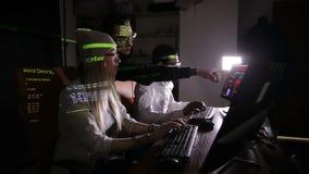 Équipe de professionnels IT multi-ethniques travaillant avec des ordinateurs dans foncé, entaillant le système informatique clips vidéos