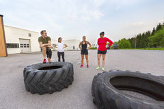 Équipe de séance d'entraînement faisant une pause de renverser la formation de pneu extérieure images libres de droits