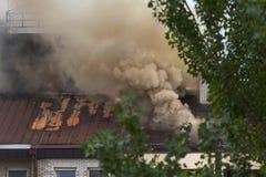 Équipe de sapeurs-pompiers au travail sur le toit en vrai état Image stock