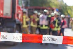 Équipe de sapeurs-pompiers par le firetruck sur l'emplacement d'accidents Photographie stock libre de droits