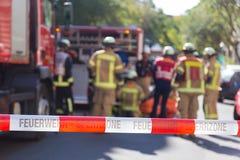 Équipe de sapeurs-pompiers par le firetruck sur l'emplacement d'accidents Photo stock