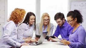 Équipe de sourire avec des ordinateurs de PC d'ordinateur portable et de table banque de vidéos