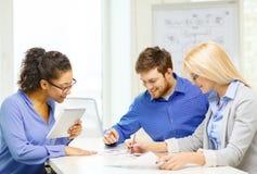 Équipe de sourire avec le travail de PC et de papiers de table Photo stock