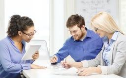 Équipe de sourire avec le travail de PC et de papiers de table Image libre de droits