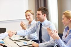 Équipe de sourire d'affaires se serrant la main dans le bureau Photographie stock