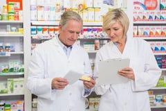 Équipe de sourire de pharmaciens parlant du médicament Images stock