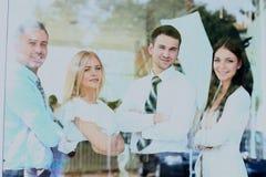 Équipe de sourire heureuse d'affaires regardant par la fenêtre Photographie stock libre de droits