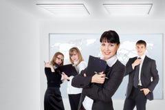 Équipe de sourire heureuse d'affaires se tenant dans une rangée au bureau photo stock