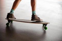Équipe des jambes dans des espadrilles se tenant sur un longboard Image libre de droits