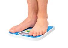 Équipe des jambes, pesées sur l'échelle de plancher. Image libre de droits