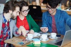 Équipe des jeunes se réunissant pour le travail en café Image stock