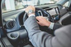 Équipe des mains sur le volant de la nouvelle électro voiture Image libre de droits