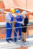 Équipe discutant la construction ou établissant des plans de situation Image libre de droits