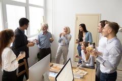 Équipe diverse amicale d'affaires parlant et riant mangeant de la pizza Photos stock