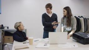 Équipe diverse d'affaires travaillant sur de nouvelles idées pour leur magasin d'habillement banque de vidéos