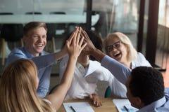 ?quipe diverse d'employ?s donnant haut cinq au briefing photographie stock libre de droits