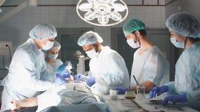 Équipe diverse de chirurgien, d'assistants et d'infirmières faisant la chirurgie envahissante banque de vidéos