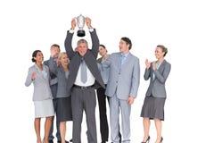 Équipe enthousiaste d'affaires encourageant à l'appareil-photo avec le trophée Images libres de droits