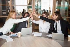 Équipe enthousiaste de travail donnant à haute cinq achievemen partagés de célébration photo libre de droits