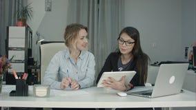 Équipe féminine de sourire d'affaires travaillant avec le PC de comprimé dans le bureau photographie stock libre de droits