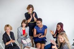 Équipe féminine multi-ethnique applaudissant pendant le séminaire d'affaires dans la salle de conférences images libres de droits