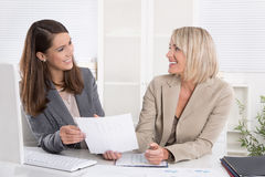 Équipe : femme d'affaires deux réussie s'asseyant au bureau ayant l'amusement à Photos stock