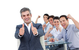 Équipe gaie d'affaires s'asseyant sur une table Image stock