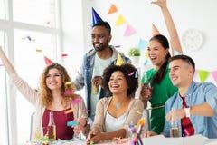 Équipe heureuse avec des confettis à la fête d'anniversaire de bureau Photo stock