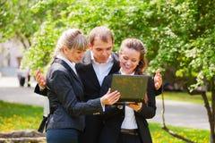 Équipe heureuse d'affaires avec l'ordinateur portatif Images stock
