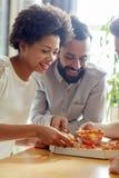 Équipe heureuse d'affaires mangeant de la pizza dans le bureau Images stock